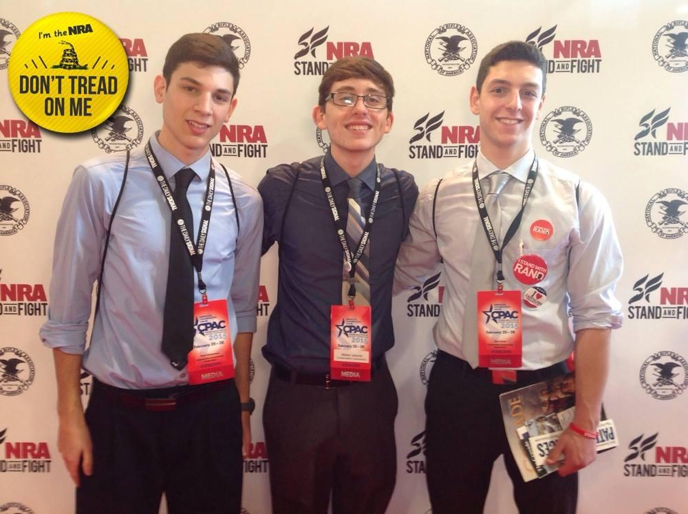 The boys posing in front of an NRA backdrop
